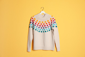 Hanger with stylish sweater on color background