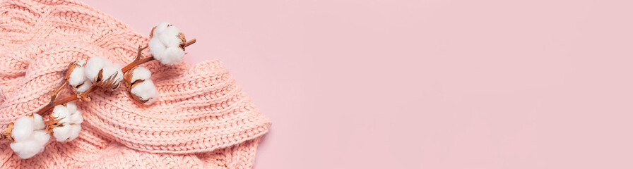 Female pink knitted sweater pullover and branch of cotton on pastel pink background top view flat lay. Fashion Lady Clothes Jumper Autumn winter clothes fashion look Delicate cotton flowers Lifestyle