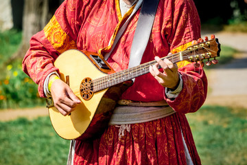 Musician in medieval bright clothes plays on lute. Festival of Medieval Music and Culture_