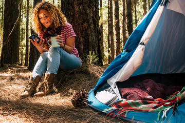 Beautiful middle age woman sitting under a pine tree in the forest use a mobile technology phone with internet connection to see the web and work like freelance independent. free camping with tent