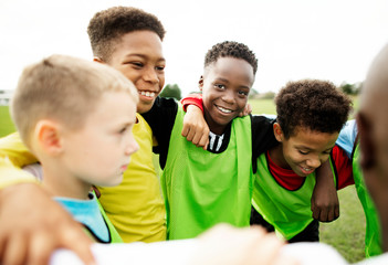 Junior football team huddling together