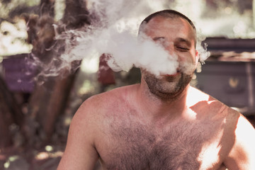 Vape man. Young man Without clothing is smoking an electronic cigarette at the summer park.