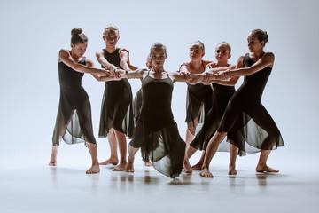 Grupa współczesnych tancerzy baletowych tańczących na szarym tle studio