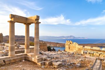 widok starożytnych portyków świątyni bogini Linda w Lindos, Rodos, Grecja, z widokiem na góry i zaskakująco piękną zatokę