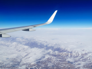 Wing of an airplane flying above the snow mountains in Southwest China. The view from an airplane window. Travel concept.