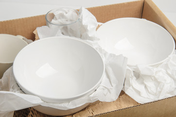 Clean white dishes in paper packed in a cardboard box. Concept relocation.