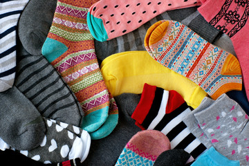 A pile of multi-colored socks. View from above. Many colorful socks form a textural background. Socks of different types and sizes.