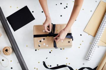 Bezpośrednio nad widokiem anonimowej kobiety wiążącej wstążkę kokardę wokół owiniętego pudełka na biały stół z dekoracjami
