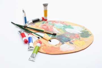 Wooden palette with brushes and acrylic paints on white background. Artistic equipment for children