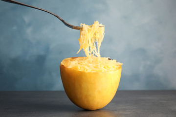 Fork with flesh over cooked spaghetti squash on table