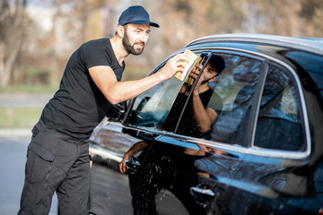 Professional washer wiping a car window with yellow sponge, washing luxury car outdoors