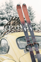 Classic car with vintage ski's and sled during snowfall