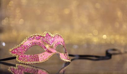 Carnival mask on golden bokeh background, copy space