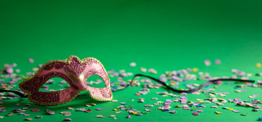 Carnival mask and confetti on green background, banner