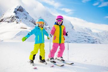 Zimowa zabawa na nartach i śniegu dla dzieci. Dzieci na nartach.