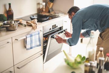 Portrait of gentleman in denim shirt closing door of oven while looking at frying pan with beef steak