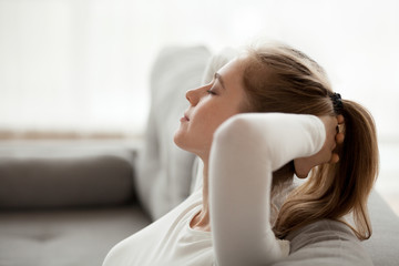 Close up of calm young female relax on cozy couch with eyes closed, peaceful girl lying on sofa hands over head having rest at home, dreamy woman stretching enjoying weekend morning in apartment