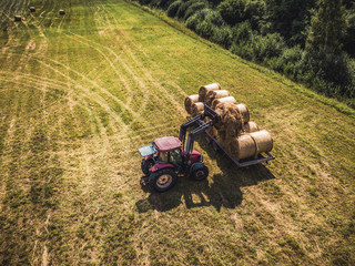 Aerial Drone Photo of Farmer Harvesting Hay Rolls in the Wheat Field with a Red Tractor