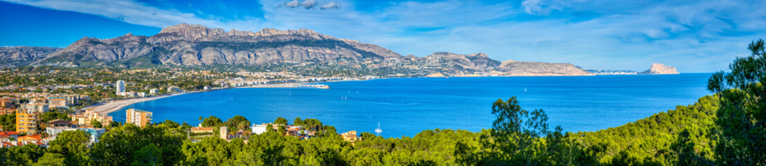 A panoramic view of Altea and the Costa Blanca from the Natural Park Serra Gelada with a bright blue ocean and sky and the mountains and towns of the surrounding area and the green trees of the park