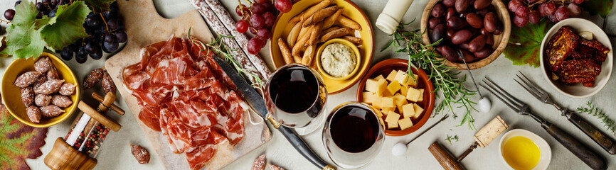 Wine and tapas on concrete background, top view