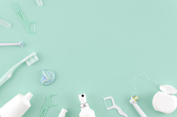 Flat lay composition with manual toothbrushes and oral hygiene products on mint background Stomatologist mock up copy space. Teeth care Frame concept