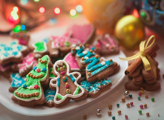 Christmas gingerbread cookies decorated with colored frosting for new year, Christmas party, winter holiday, sweet home gift for kids. Balls and garlands Christmas background.
