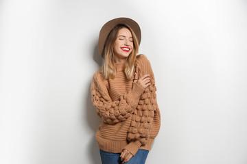 Piękna młoda kobieta w ciepłym pulowerze z kapeluszem na białym tle