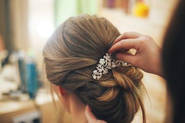 Fryzjer robi fryzurę dla młodej dziewczyny. Ścieśniać