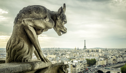Gargoyle on the Cathedral of Notre Dame de Paris looks at the Eiffel Tower, Paris, France