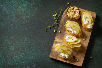 Antipasti snacks for Wine. Brushetta with Soft Cheese and Pear served on a rustic wooden board on a stone table. Top view flat lay background. Copy space.