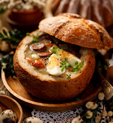 The sour soup (Żurek) made of rye flour with smoked sausage and eggs served in bread bowl. Traditional polish sour rye soup, popular Easter dish