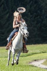 Junge Frau mit Cowboyhut  galoppiert  im Westernstil auf ihrer Araberstute
