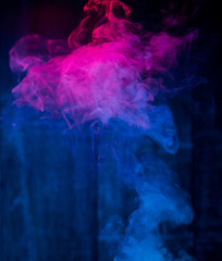 red and blue smoke patterns at dark background