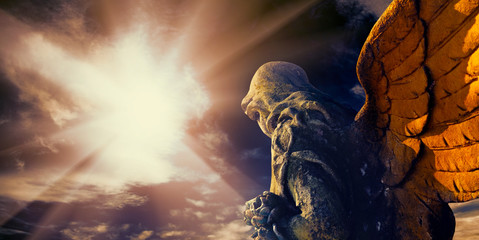 Antykwarska statua anioł stróż w świetle słonecznym.