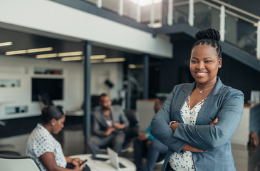 Portrait of a confident black businesswoman with all african american team in the background