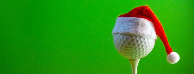 Piłka golfowa zamontowana na koszulce ma na sobie pamiątkowy kapelusz Świętego Mikołaja. Blank na pocztówkę dla golfisty z okazji Nowego Roku i Bożego Narodzenia. Jasne zielone tło. Skopiuj miejsce