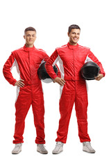 Two young racers standing and holding helmets
