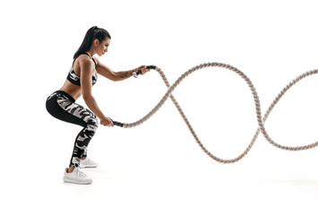 Strong muscular woman working out with battle ropes. Photo of attractive woman in fashionable sportswear isolated on white background. Strength and motivation. Side view.