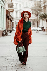 Outdoor full body fashion portrait of young beautiful woman wearing trendy oversized orange faux fur coat, hat, green sweater, corduroy trousers, holding stylish snakeskin bag, posing in street