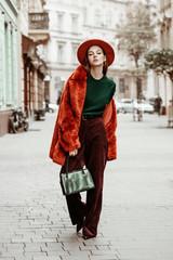 Outdoor full body fashion portrait of young beautiful woman wearing trendy oversized orange faux fur coat, hat, green sweater, corduroy trousers, holding stylish snakeskin bag, posing in street
