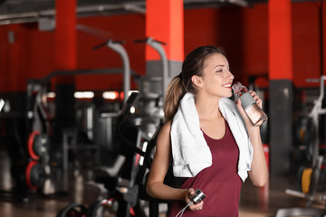 Beautiful young woman with towel and bottle of water in gym. Space for text