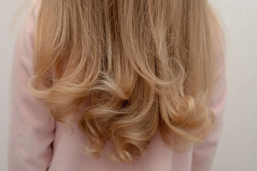 A girl is standing back with beautiful curly hair