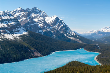 Spring aerial view of the Peyto lake and snowy rocky mountains in background - Banff national park, Alberta, Canada. Shot was taken in late spring and the lake is still half frozen.