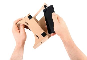 Man putting smartphone into cardboard virtual reality headset on white background, closeup