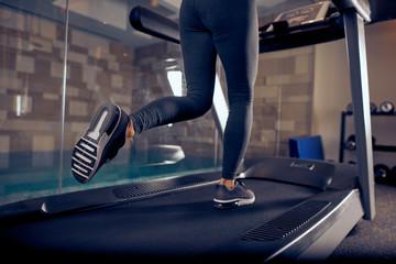 Close up of woman's legs running on treadmill. Gym interior.