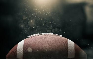 Futbol amerykański piłka na czarnym tle oświetlony przez