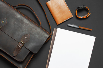 Fashionable concept. Brown leather men's bag, wristwatch, leather passport cover, pen, blank white sheets on black background top view flat lay with copy space. Accessories businessman stylish clothes