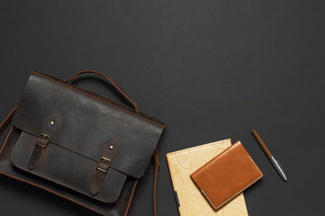 Fashionable concept. Brown leather men's bag, diary notebook, leather passport cover and pen on black background top view flat lay with copy space. Accessories businessman, stylish men's clothes