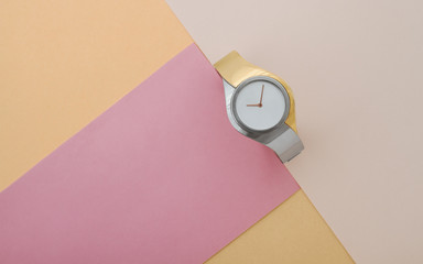 Silver and gold modern wrist watch on pink and peach color background top view