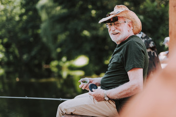 Positive elderly man enjoying his fishing weekend while holdign a rod